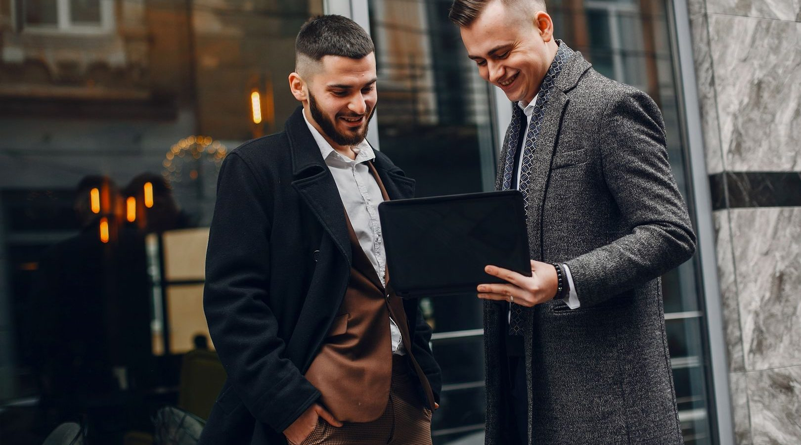 Two handsome men working. Friends talking. Man in a suit and coat