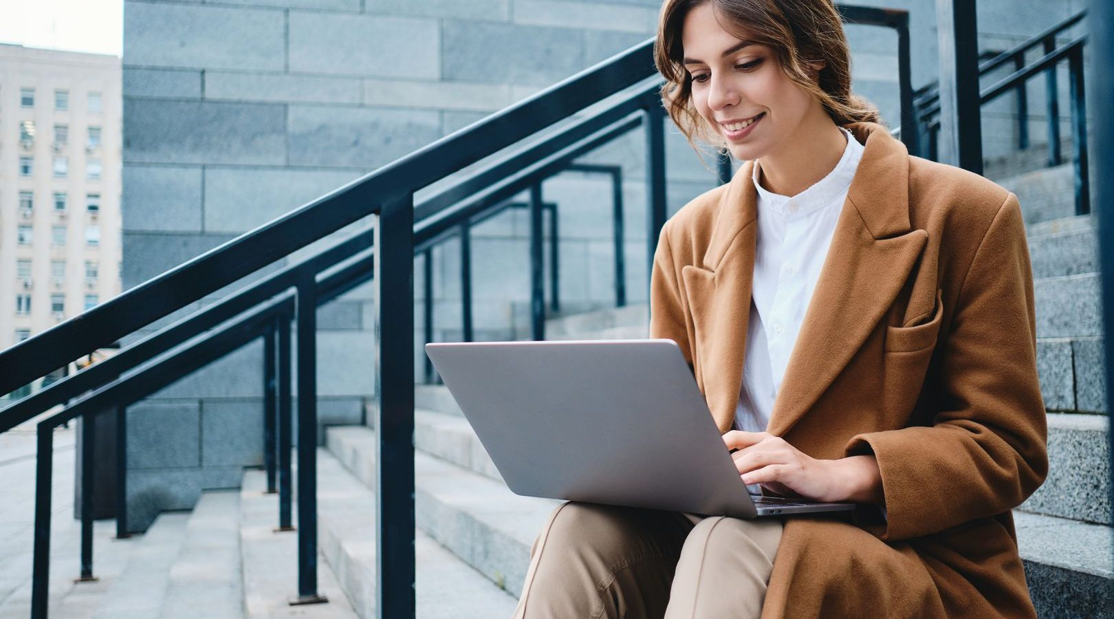 Young attractive smiling businesswoman in coat happily working with laptop on stairs on street